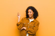 canvas print picture - young pretty black woman smiling happily and looking sideways, wondering, thinking or having an idea against orange wall