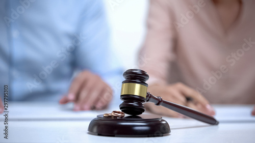 Marriage rings and gavel closeup, spouses signing divorce document on background