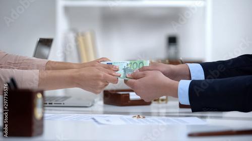 Photo Man and woman hands pulling euro money, dividing marital property during divorce