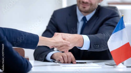 Fotografía French official signing docs about state business support, shaking partner hand