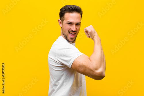 young handsome man feeling happy, satisfied and powerful, flexing fit and muscul Wallpaper Mural