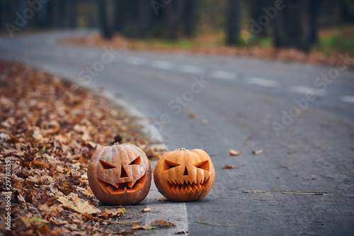 Fotografía  Two Halloween Pumpkins on the side of the road in the forest