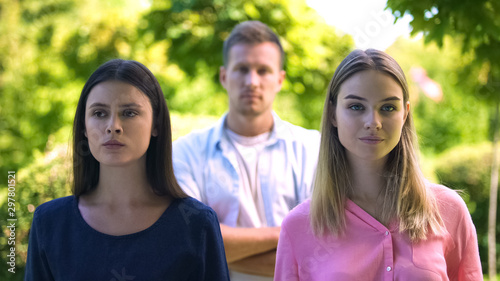 Brunette and blond females with man on background, relations conflict, jealousy Canvas Print