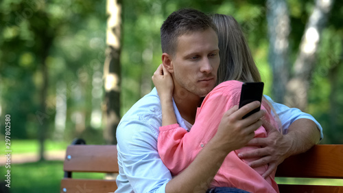 Fotomural Boyfriend texting message another woman while hugging girlfriend, betrayal