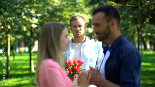Cuadros en Lienzo Disappointed man with flowers looking at girlfriend flirting with another man