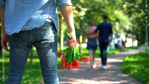 Fotografía Man with flowers looking girlfriend hugging another male, love disappointment