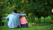Loving male and female hugging sitting on grass in park, couple togetherness