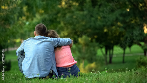 Fotografía Loving male and female hugging sitting on grass in park, couple togetherness