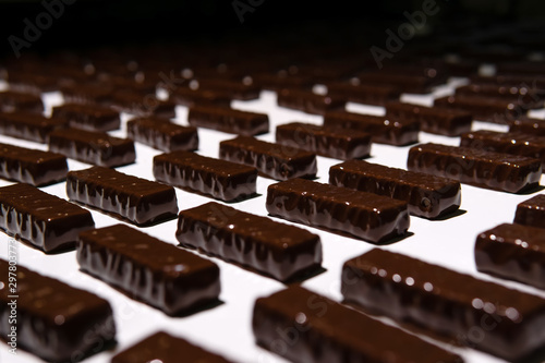 obraz lub plakat chocolate candies on the conveyor of a confectionery factory close-up