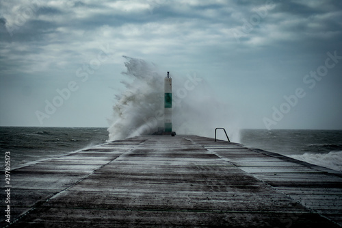 Obraz Strong winds create big waves that batter into Aberystwyth, Mid Wales sea front during the Storm season. - fototapety do salonu