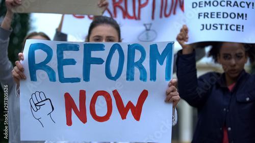 Fototapeta Activist showing banner Reform now, protesting corruption, unfair justice