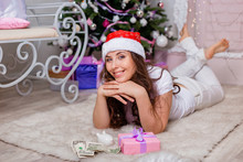 A Young, Beautiful Girl In White Clothes And A Red Hat Lies On The Fur Next To A Gift, A Piggy Bank And Dollars Against The Background Of A Christmas Tree And A Fireplace.