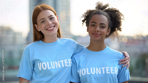 Two female volunteers smiling on camera, high school charity program, altruism Canvas Print
