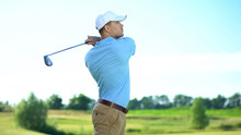 Professional Golfer Hitting Ball In Swing Position, Looking At Meadow, Sport