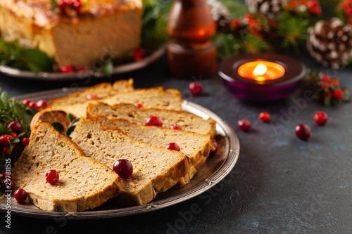 Delicious chicken and pork pate in Christmas decoration. Rustic style. Dark background, metal plates. Front view.