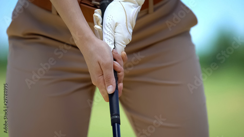Female in white glove with golf club studying to play basic ball position, sport Canvas Print