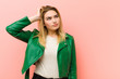 Leinwanddruck Bild - young pretty blonde woman feeling puzzled and confused, scratching head and looking to the side against pink flat wall