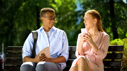 Fotografie, Tablou  Mixed-race boy trying to get acquainted with gadget-addicted girl, she refusing