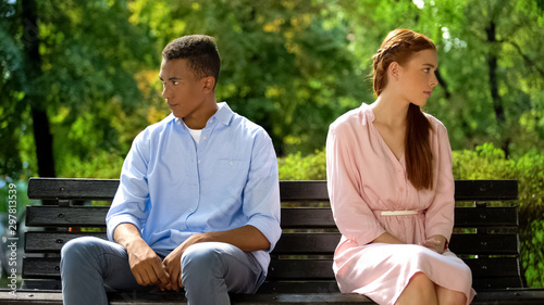 Foto  Offended teenagers sitting on bench turned from each other, misunderstanding