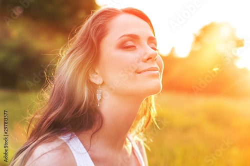 Fotografía Young woman on field under sunset light