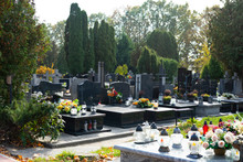 Graves At A Christian Cemetery In Autumn. All Saints Day. Tombstones Decorated With Flowers And Grave Candles.