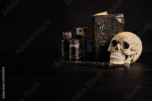 Obraz na plátně Realistic model of a human skull with teeth on a wooden dark table, black background