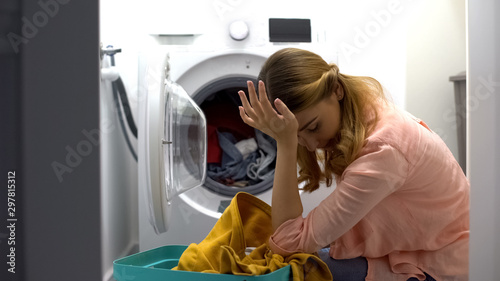 Pinturas sobre lienzo  Tired woman loading clothes in washing machine, annoyed with housework routine