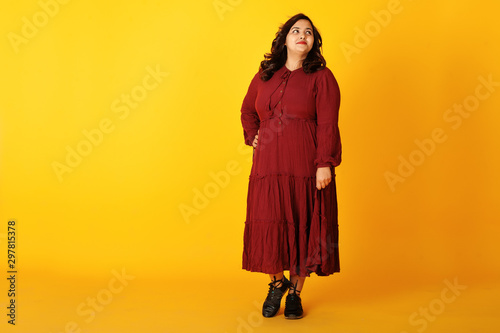 Fotografía Attractive south asian woman in deep red gown dress posed at studio on yellow background