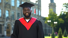 Happy Afro-american Student In Graduation Gown Sincerely Smiling On Camera