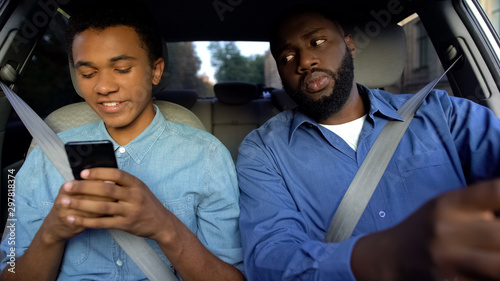 Joyful afro-american teen texting phone dad trying to read message while driving Fototapet
