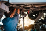 Mechanic repairing a car, Mechanic inspects car suspension system and chassis with a torch-lite under the car.