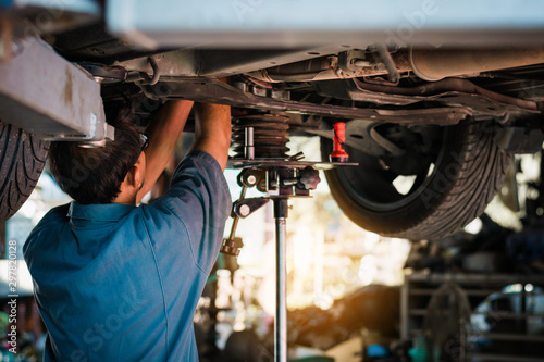 Mechanic repairing a car, Mechanic inspects car suspension system and chassis with a torch-lite under the car. - 297820128