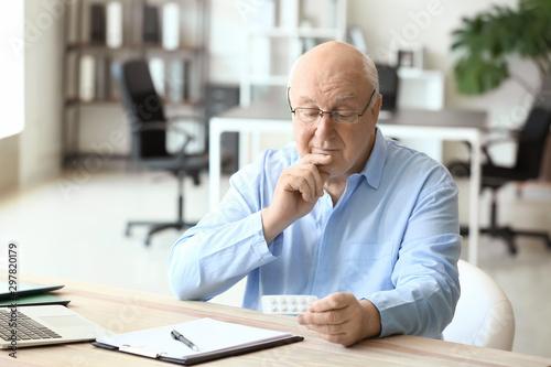 Fotografia  Elderly man taking medicine in office