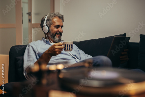 Leinwand Poster man listening music on headphones in his home