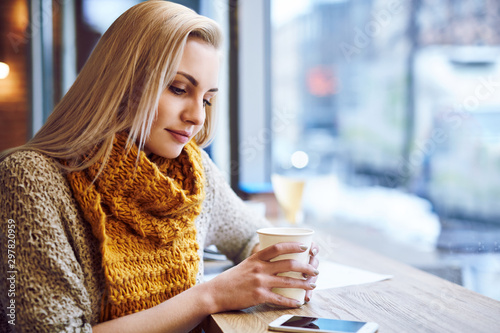 Foto  Beautiful young woman warming up in cafe during cold winter day.