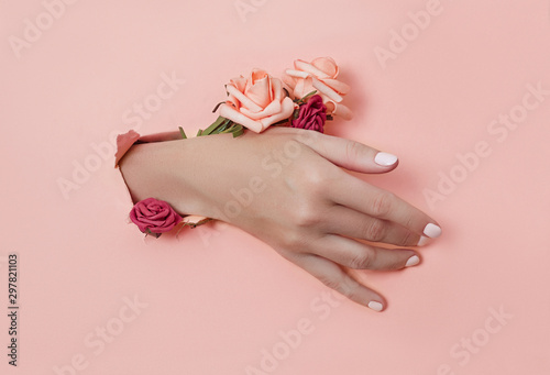 Hand with paper flowers and painted nails is thrust through a hole in the paper background. Cosmetics and hand care, moisturizing and wrinkle reduction - 297821103