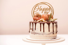 Birthday Cake Decorated With Golden Macaroons And Chocolate Pieces. Elegant Naked Cake Topped By Chocolate. Birthday Party Celebration