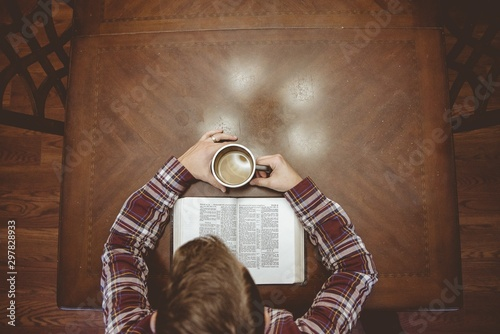 Photo Overhead shot of a male holding his coffee while reading the bible