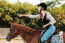 Image Of Woman Wearing Hat Pointing Finger While Riding Horse At Yard