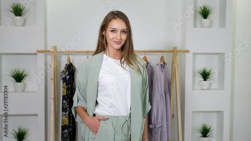 Obraz na plátně beautiful lady with loose hair and nice smile in fair pantsuit standing against