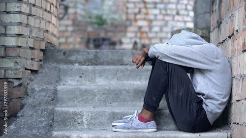 Tableau sur Toile Lonely male teen sitting building stairs, misunderstanding depression, problem