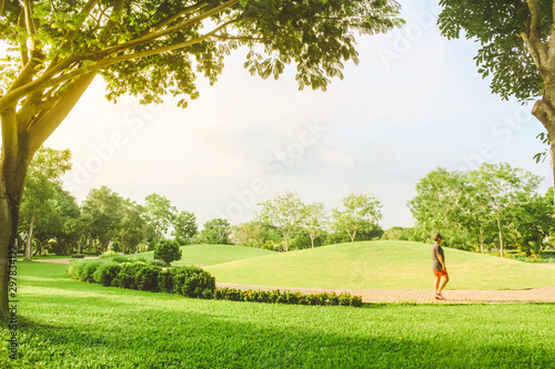 Foto op Canvas Zwavel geel A man walking under beautiful pure sunrise morning in public park with green grass, tree and flower. Half moon park in Ho Chi Minh city, Vietnam.