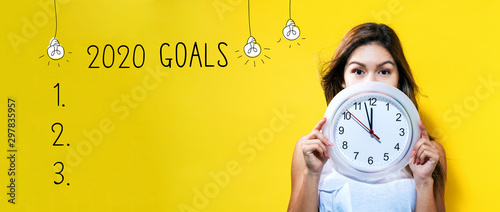 Obraz na plátně  2020 goals with young woman holding a clock showing nearly 12