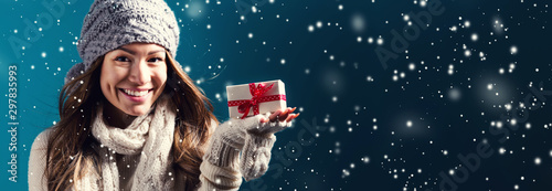 Foto  Happy young woman holding a Christmas present