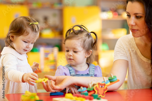 Foto auf Gartenposter Individuell Children and nursery teacher play with toys in kindergarten playroom