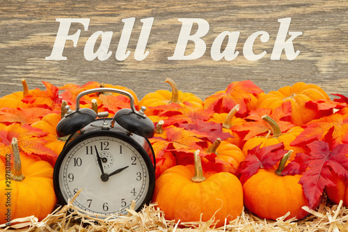 Fall Back time change message with a retro alarm clock with pumpkins and fall leaves - 297838102