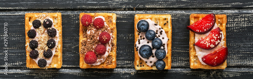 Cuadros en Lienzo Homemade waffles with blueberries, raspberries and peaches on a black wooden rustic background,border