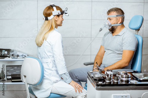 Photo Adult man during a medical breathing treatment with respiratory mask against sno