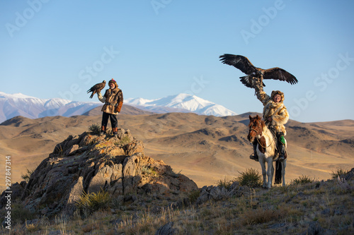 Photo Two old traditional kazakh eagle hunters posing with their golden eagle in the mountains