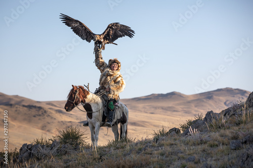 Old traditional kazakh eagle hunter posing with his golden eagle in the mountains. Ulgii, Western Mongolia. - 297847350